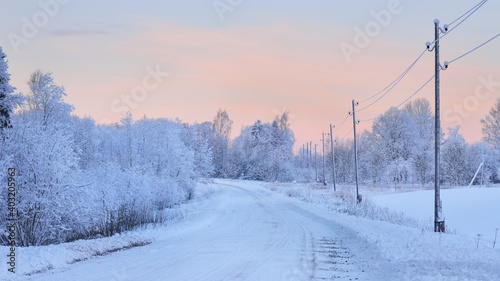 Panoramic view of the snow-covered rural road at sunset. Electricity line. Winter wonderland. Christmas, tourism, seasons, nature, landscape, off-road, logistics, remote places, communications