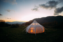 Night Time Sunset Shot Of Glamping Camping Tent Set Up In Beautiful Nature Landscape. Cosy And Warm Big Tent Lit From Inside With Orange Dimmed Lights. Romantic Weekend Getaway For Couple