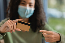 African American Woman In Medical Mask Pointing With Finger At Credit Card