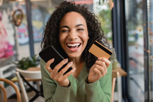 Cheerful African American Woman Laughing While Holding Smartphone And Credit Card