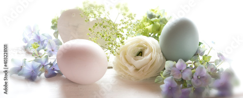 Easter still life with pastel colored eggs and tender blossom on a white table. Background with short depth of field for easter greetings with a heart and space for text.