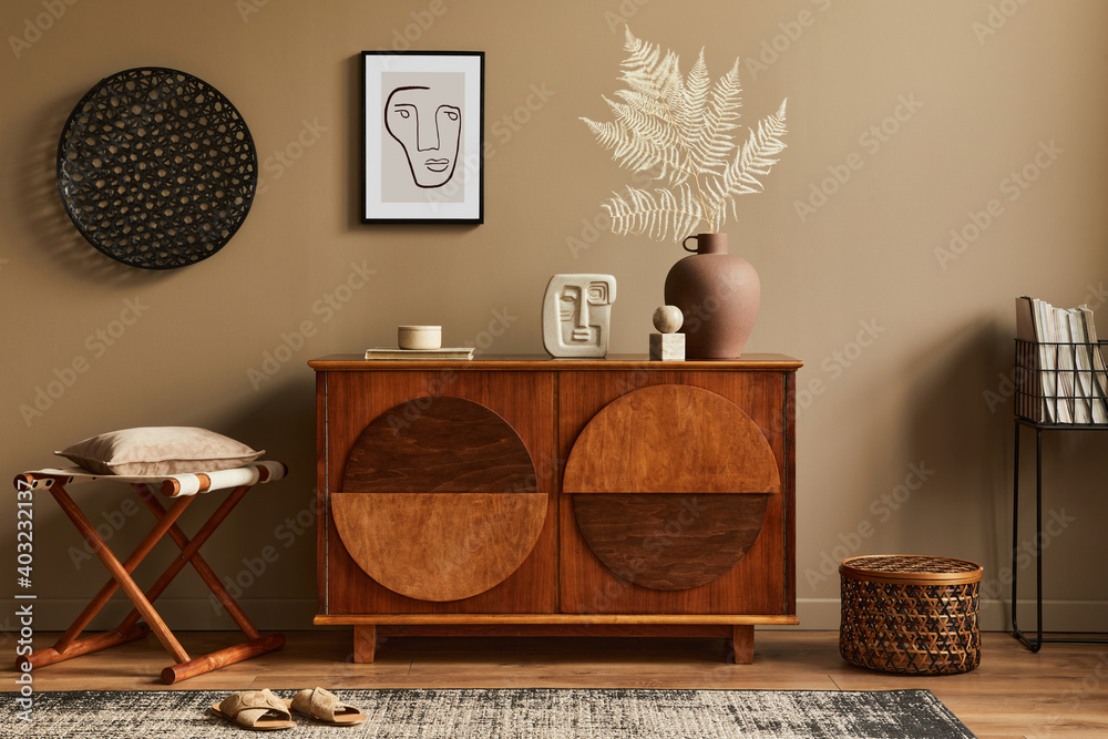 Fototapeta Stylish interior with design wooden commode, stool, dried flowers in vase, unique decoration, carpet, mock up poster frame and elegant personal accessories. Modern living room in classic house.