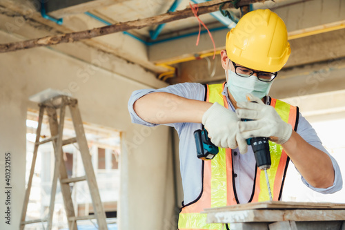 Obraz Construction foreman worker in hardhat safety helmet drilling by electric drill on the construction site. wearing surgical face mask during coronavirus covid and flu outbreak - fototapety do salonu