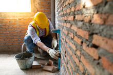 Man Bricklayer Installing Bricks On Construction Site