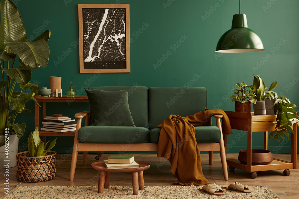Fototapeta Stylish living room in house with modern retro interior design, velvet sofa, carpet on floor, brown wooden furniture, plants, poster mock up map, book, lamp and perosnal accessories in home decor.