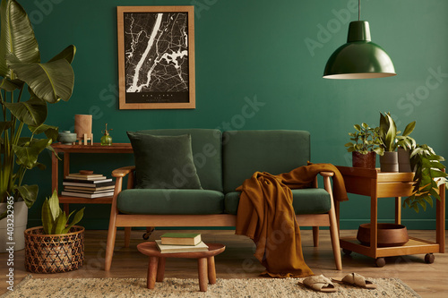 Stylish living room in house with modern retro interior design, velvet sofa, carpet on floor, brown wooden furniture, plants, poster mock up map, book, lamp and perosnal accessories in home decor.