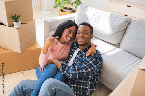 Obraz na plátně Black millennial lady with her husband hugging and holding house key in their ne