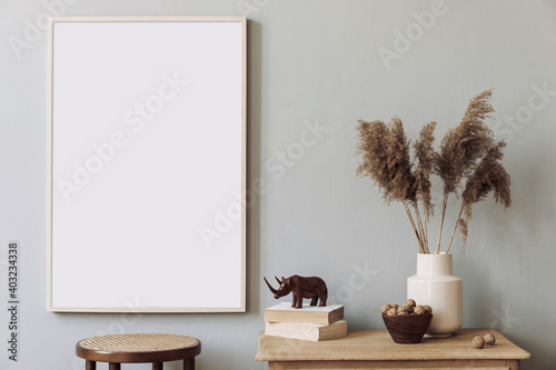 Minimalistic composition of living room interior design with mock up poster frame, flowers in vase, chair and elegant accessories. Stylish home decor. Template. Gray background walls.