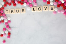 The Words True Love Written In Scrabble Tiles On A Marble Kitchen Counter Top Surrounded By Valentines Candy