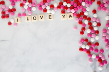 The Words I Love Ya Written In Scrabble Tiles On A Marble Kitchen Counter Top Surrounded By Valentines Candy