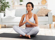 Reaching inner peace and harmony. Positive black woman meditating with closed eyes, doing breathing exercies at home
