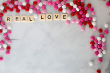 The Words Real Love Written In Scrabble Tiles On A Marble Kitchen Counter Top Surrounded By Valentines Candy