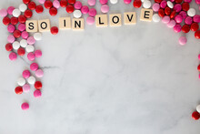 The Words So In Love  Written In Scrabble Tiles On A Marble Kitchen Counter Top Surrounded By Valentines Candy