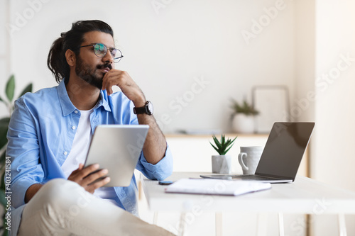 Canvas Print Pensive Young Arab Male Freelancer Using Gigital Tablet And Daydreaming At Home