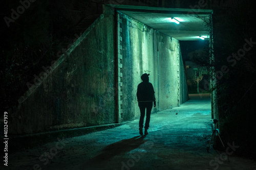 Canvas Print Lonely woman walking in a dramatic mystic dark alley at night