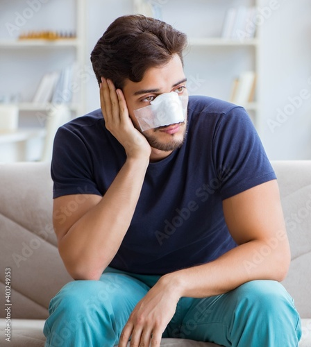 Young man recovering healing at home after plastic surgery nose Fototapeta