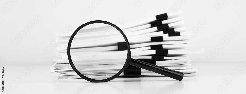 Fototapeta Stack of report paper documents with magnifying glass. Concept of business and search.