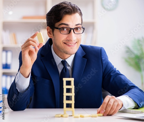 Foto Young businessman building domino tower in office