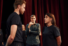 Two People Talking. Group Of Actors In Dark Colored Clothes On Rehearsal In The Theater