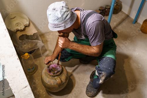 Obraz na plátně Man making pickles in a ceramic vasel using an old recipy