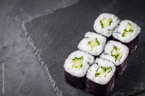 Fototapeta appetizing sushi roll maki with cucumber on a black stone plate obraz