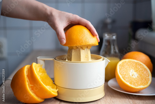 Fototapeta Female hand squeezing orange juice. obraz