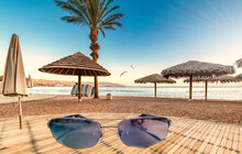 Digitally Composite Image With Sunglasses As Foreground. Morning At Sandy Beach Of The Red Sea, Middle East