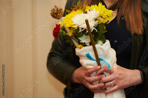 Canvas Print Female hands holding bouquet of flowers with candle in the church at baptism