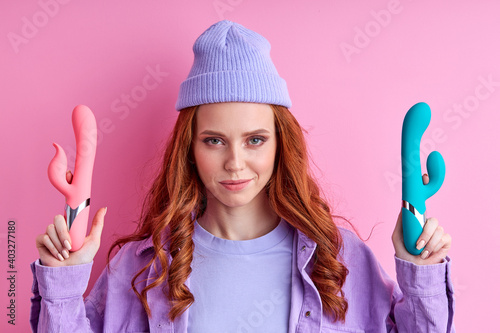 woman enjoys sexual life poses with vibrators to satisfy all types of preferences, have fun posing at camera isolated on pink background