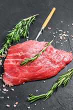 Raw Flat Iron Steak With Rosemary And Pink Salt. Fresh Marble Beef Meat Black Angus. Black Background. Top View