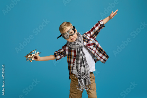 happy child boy in retro glasses and scarf playing with wooden toy airplane on blue background. dream of becoming a pilot