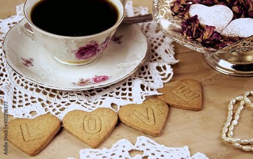 LOVE ciasteczka serca z napisem na drewnianym tle, filiżanka z kawą, płatki róż, perełki, Walentynkowe ciasteczka, vintage
