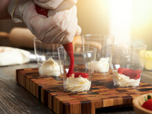 A Closeup Of A Pastry Chef Filling Cups With Trifles