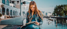 Back To School Student Teenager Girl Reads A Textbook. Outdoor Portrait Of Young Teenager Brunette Girl With Long Hair. Girl On City
