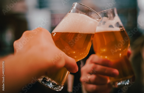 Obraz Close-up view of a two glass of beer in hand. Beer glasses clinking in bar or pub - fototapety do salonu
