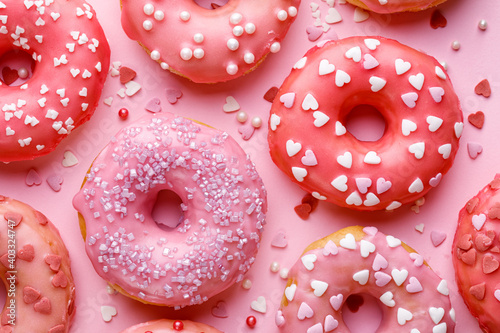 Valokuva Sweet donuts with pink glaze decorating sprinkles on a pink background, top view