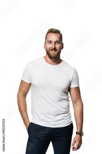 Obraz Relaxed attractive blonde bearded man standing against a white background wearing a white t-shirt, smiling towards camera. - fototapety do salonu