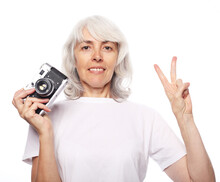 Lifestyle And People Comcept: Happy Elderly Woman Is Holding A Camera And Smiling. Shows The Sign Of Victory.