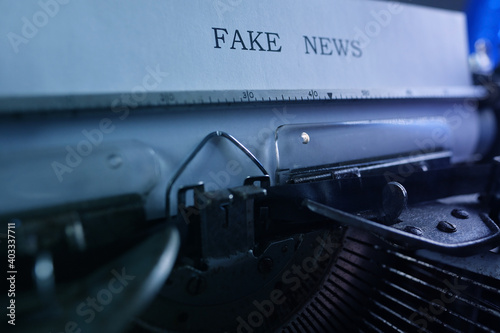 old typewriter on table, words fake news are printed on paper in large size, can Poster Mural XXL