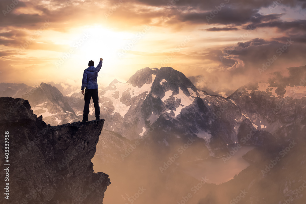 Fototapeta Fantasy Adventure Composite with a Man on top of a Mountain Cliff with Dramatic Landscape in Background during Sunset or Sunrise. Landscape from British Columbia, Canada.