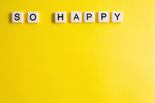 The Words So Happy Written As A Flat Lay In Wood Scrabble Tiles On A Plain Yellow Background