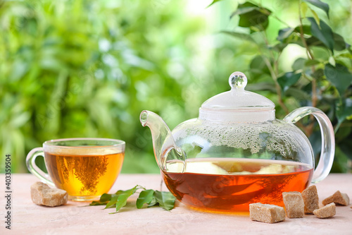 Obraz Teapot and cup of tea on table against blurred background - fototapety do salonu