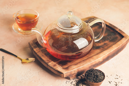 Glass teapot and cup of tea on table