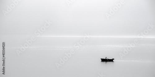 Fototapeta Rowing boat lonely on a misty sea