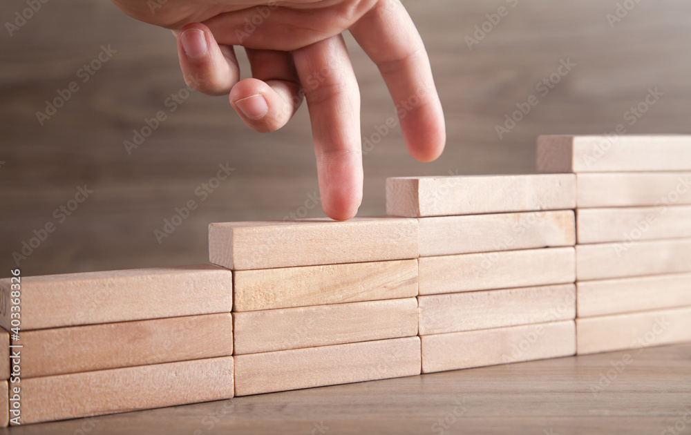 Fototapeta Fingers climbing the stairs made with wooden blocks.