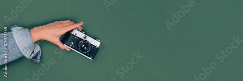 Obraz Banner with female hand holding old retro photo camera on green background with copy space for text. Trendy vintage photography, Online photography school concept, selective focus - fototapety do salonu