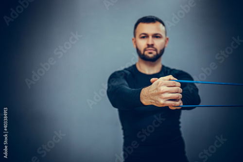 Fototapeta Athletic bearded man doing lunge workout exercise with resitance band in gym on grey background