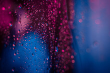 Dramatic Neon Lighted Window With Rain Drops. Bright Neoned Colors. Scary And Horror Concept.