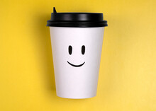 White Cardboard Cup With Black Lid With Smiling Face On Yellow Background