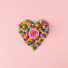 Creative Heart Shape Made With Colorful Chocolate Candy Drops With Rose In Center Against Pink Background. Sweet Valentine's Day Concept.